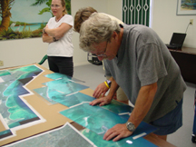 Dr Donald Keith explains the East Caicos coastline to Richard Coberly (pictured examining the photos in detail) and the rest of the team earlier this week. The photo montage will be displayed on the boat alongside more technological GPS visual wizardry